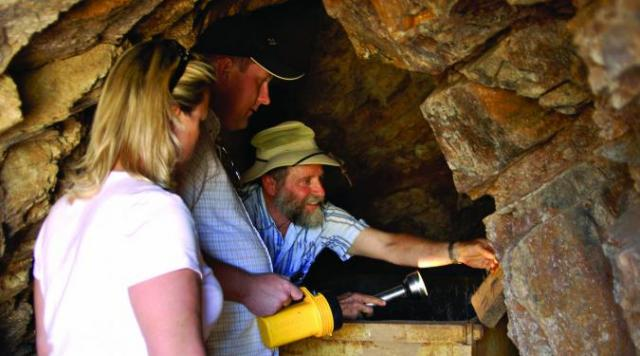 Prospector with guests in Parabonito mine shaft 500 ft deep